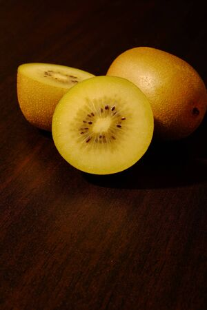 Fresh yellow kiwi(or gold kiwi) and cut yellow kiwi with space for text on wooden table top.