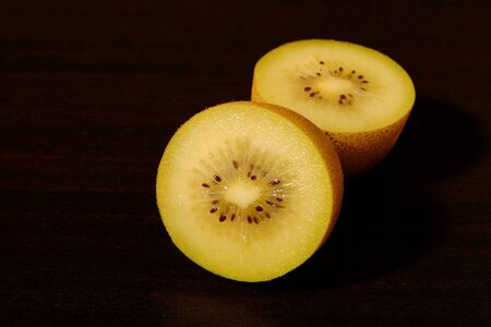 Fresh yellow kiwi(or gold kiwi) and cut yellow kiwi with space for text on dark table top.