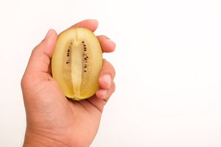 Healthy, eating and diet concept; Idea with hand holding half ripe yellow kiwi (or gold kiwi) on white background.