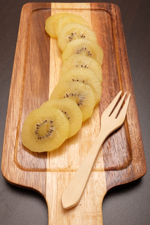 Healthy, eating and diet concept; Idea with slice of ripe yellow kiwi(or gold kiwi) in wooden plate on dark table top.