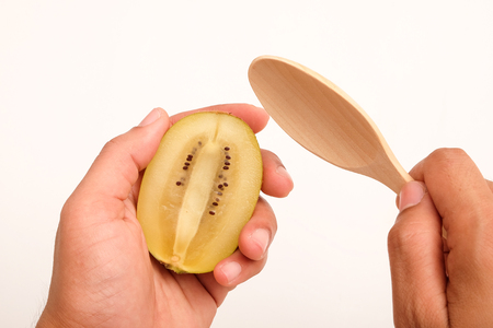 Healthy, eating and diet concept; Idea with hand holding half ripe yellow kiwi (or gold kiwi) and wooden spoon on white background. Reklamní fotografie