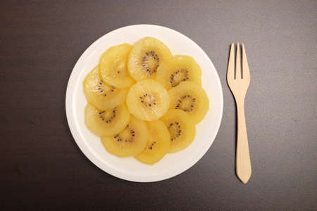 Healthy, eating and diet concept; Idea with slice of ripe yellow kiwi(or gold kiwi) in white plate on dark table top.