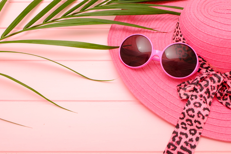 Summer concept; Idea with pink collection summer hat and sunglasses on pink wooden.