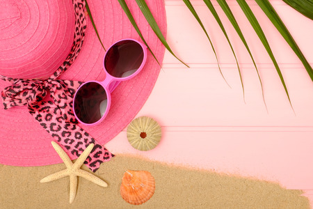 Summer concept; Idea with pink summer hat, pink sunglasses, sand, sea shell and starfish on pink wooden.