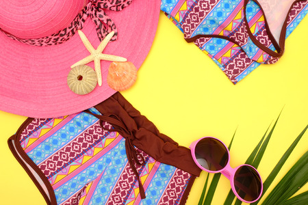 Summer fashion: Clothing and accessories for beach on yellow background.