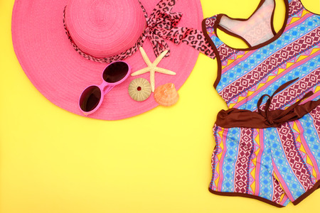 Summer fashion: Clothing and accessories for beach with space for text on yellow background.