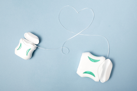 Dental care; Dental floss on light blue background. Redakční