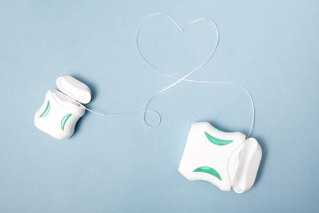 Dental care; Dental floss on light blue background. Editorial
