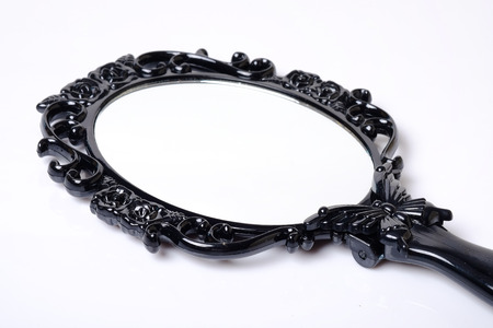 Close up of black vintage hand mirror on white background.