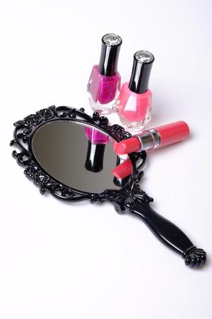 Black vintage hand mirror, lipstick and nail polish on white background. Redakční