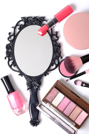 Black vintage hand mirror with cosmetics makeup on white background.
