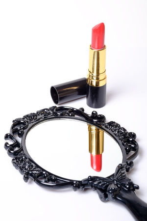 Black vintage hand mirror and lipstick on white background. Editorial