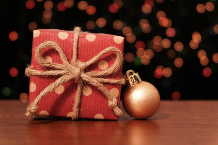 Gift box and christmas ball on wooden table in front of light bokeh background Standard-Bild