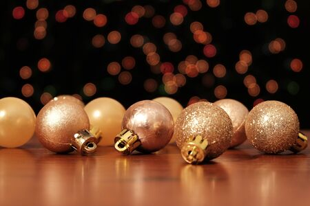 Christmas balls on wooden table in front of light bokeh background