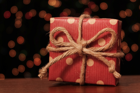 Gift box on wooden table in front of light bokeh background