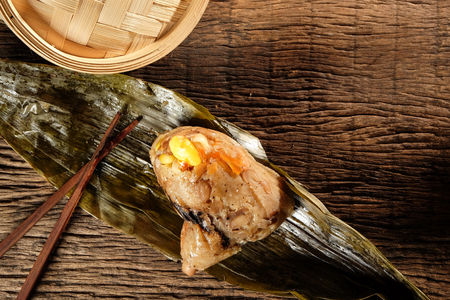 Top view of Zongzi or Traditional Chinese Sticky Rice Dumplings on wooden table with space for text. Background for dragon boat festival.