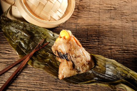 Zongzi or Traditional Chinese Sticky Rice Dumplings on wooden table with space for text. Background for dragon boat festival. Reklamní fotografie