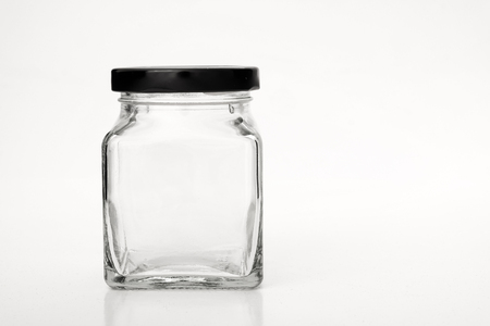 Square empty glass jar with black lid with space for text on white background.