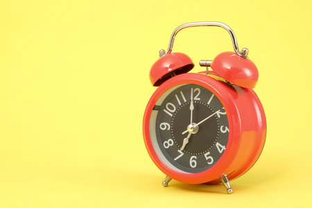 Red vintage alarm clock with space for text on yellow background. Reklamní fotografie