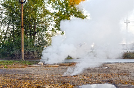 Rush of underground pipeline with hot water. Steam is rising from the sewers.