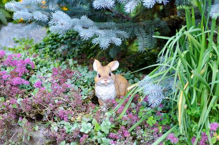 A small, artificial rabbit in the grass, under the tree. Banco de Imagens