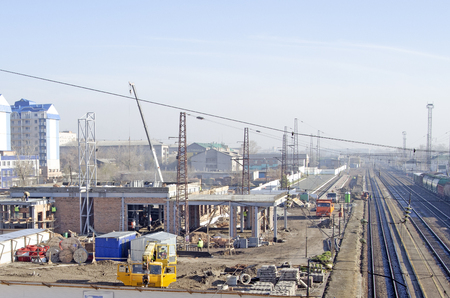 Construction site of the railway station. Truck cranes, workers and construction materials