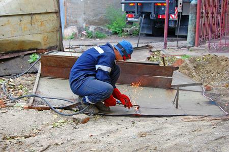 Gas welder at work. A welder cuts a sheet of metal with an autogen. Open air.