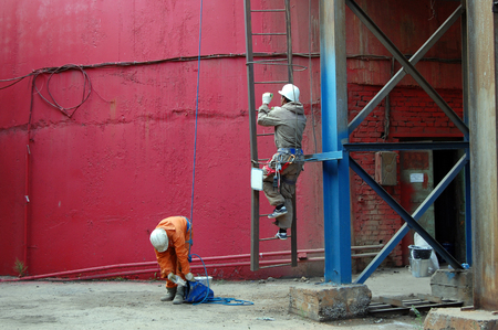 Workers climb a metal wall hanging