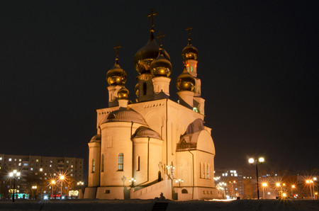 Night photo of an orthodox cathedral. Golden domes in the light of street lamps. Russia. Abakan
