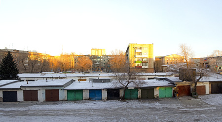 Ordinary Russian apartment buildings and cars for cars. The golden hour, before sunset.