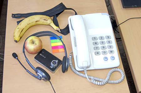 Still life on the desktop (apple, banana, headphones, telephone, DVR)