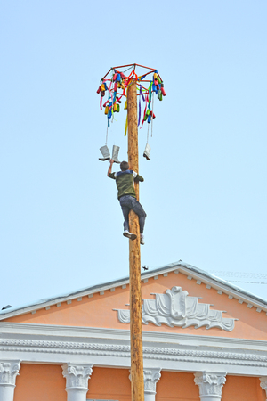 A man during the holiday climbs on the pillar