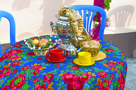 Samovar and bagels on the table, covered with a beautiful tablecloth. Festive tea party