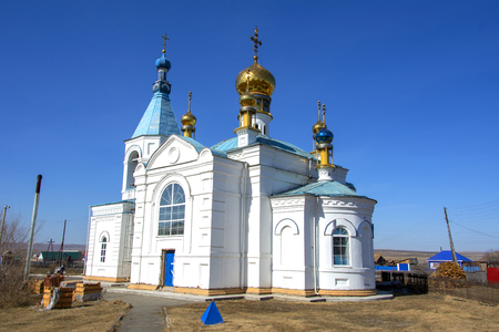 Old church with golden domes. It is built in a Siberian village. Russia.