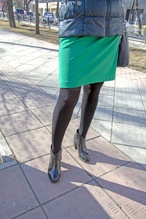 Womens legs in black nylon pantyhose in shoes with heels. On the street. Fetish.