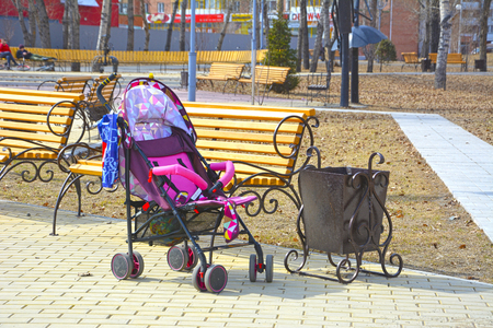Empty baby carriage in the city park near the bench. Close to the trash can