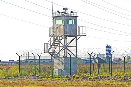 Guard tower and fence around a military unit. Russia. Siberia Imagens - 132077362