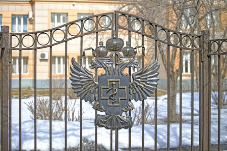 The coat of arms of Russia is forged from metal, mounted on the gates of a state organization