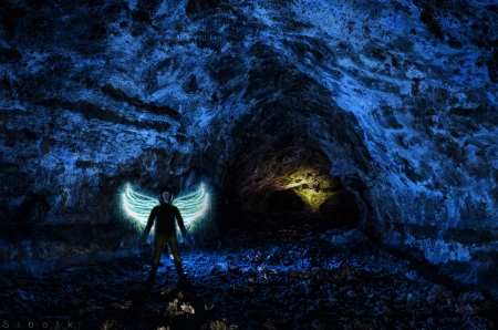 dark: An angel inside a large blue cave Stock Photo