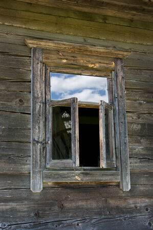 Old window on a wooden farm house wall