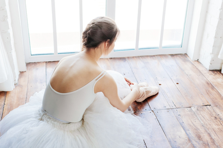 barre: Young ballerina standing on poite at barre in ballet class. Stock Photo