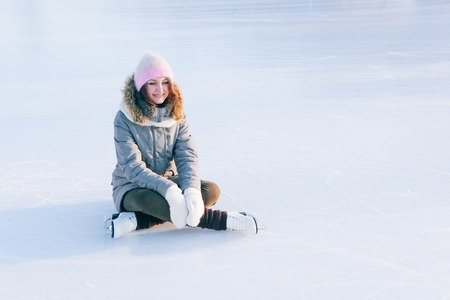 iceskates: Ice skating woman sitting on the ice smiling.
