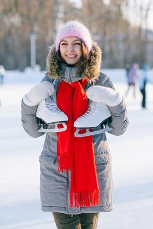 iceskates: ice skating winter woman holding ice skates outdoors in snow.