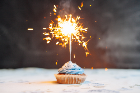 Birthday Cupcake with a sparkler over a blue background. Imagens - 56602679