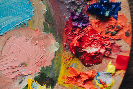 Painter mixes yellow and red oil paint on the palette. Closeup of paint mixing process in art workplace