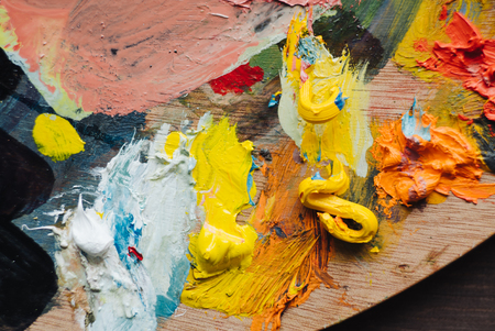 Painter mixes yellow and red oil paint on the palette. Closeup of paint mixing process in art workplace.