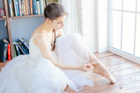 Ballet dancer tying slippers around her ankle woman ballerina pointe. Stock Photo