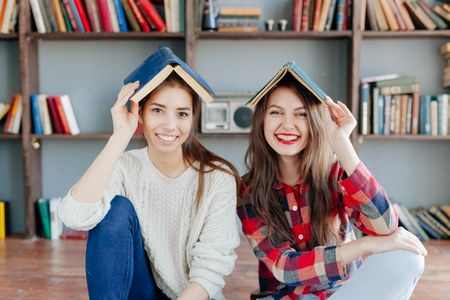 frienship: Hipster young girls hiding under the blue books.
