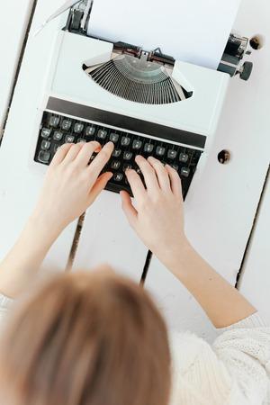 womans hand typing on white retro machine. Stock Photo