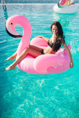 Tan girl sits on inflatable mattress flamingos in the pool Stock Photo - 65361370